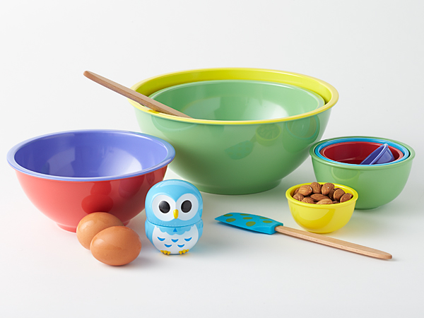 Sleek, nested melamine items: two-toned mixing bowls and multi-colored measuring cup set.  Wooden spatulas with non-stick friendly silicone heads with custom artwork, and peppy owl timer.